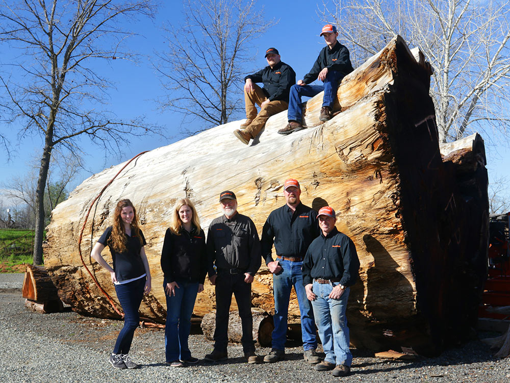 an image of the Far West staff standing in front of a very large tree trunk that is about 15 feet high, with 2 of the staff members sitting on top and 5 below on the ground level.