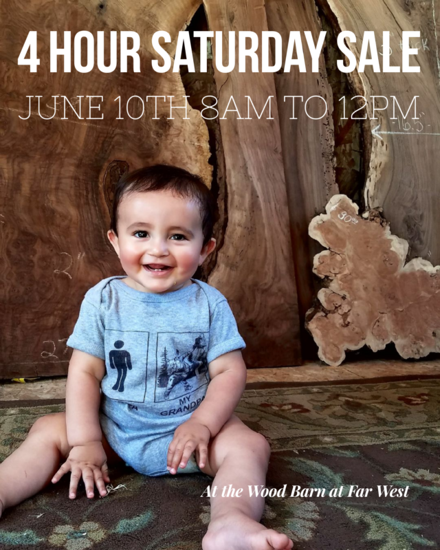 Cute baby in front of walnut lumber for Saturday 4 hour lumber sale June 10th from 8am to 12noon